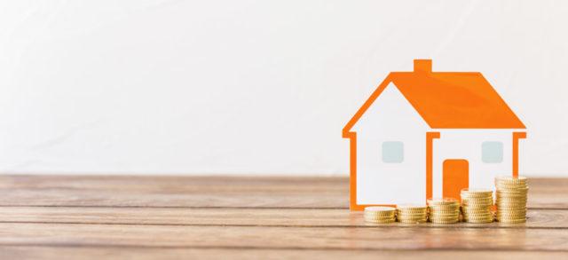 casa pequeña junto a monedas